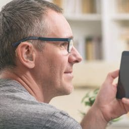 Man with hearing aid uses his phone.