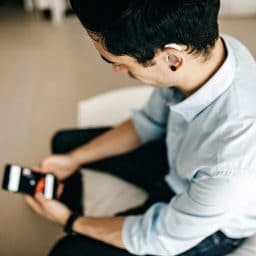 Younger man wearing a hearing aid using a smartphone.